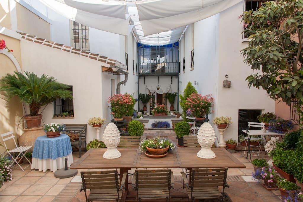 Het uitzicht vanaf het gastenverblijf op de patio en op het hoofdgebouw.