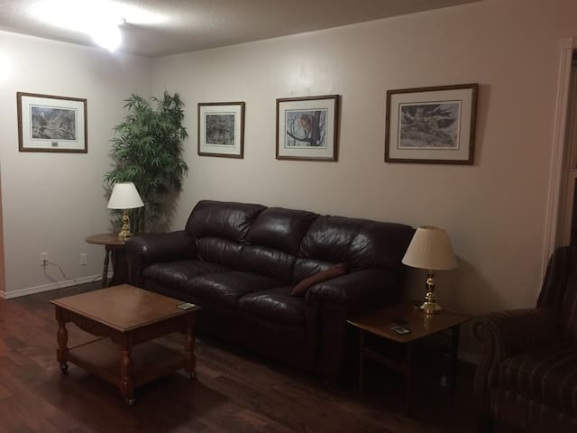 """Living Room with a comfortable leather couch and chair , nature pictures  and lamps.  There is WIFI and cable television on a 55"""" tv"""