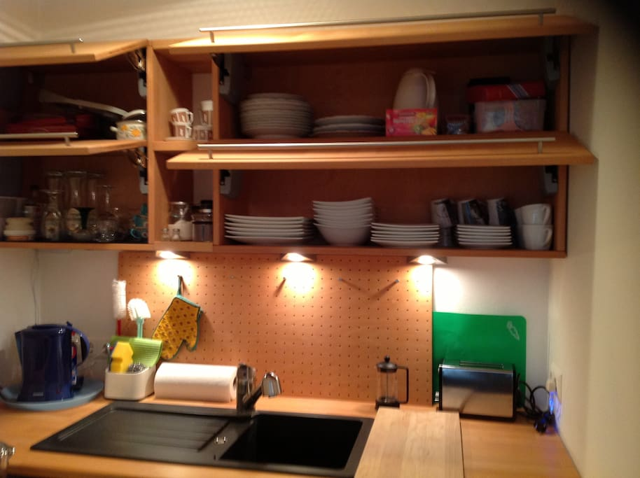 kitchenette with wooden cabinets filled with dishes, cups, glasses, brand new electric water kettle etc