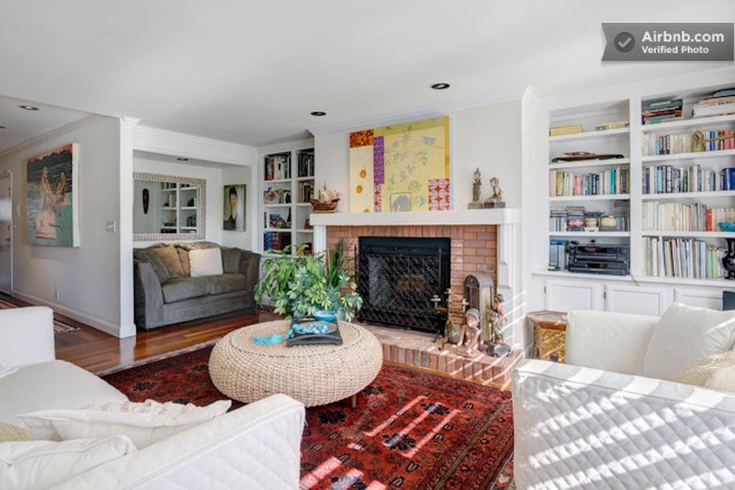Living room with comfortable sofas, reading nook with bookcases surrounding fireplace. Cosy warm atmosphere with great art.