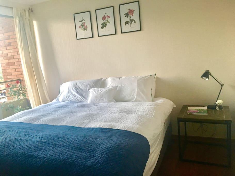 Dormitorio con cama king, ensuite y balcon con vista.