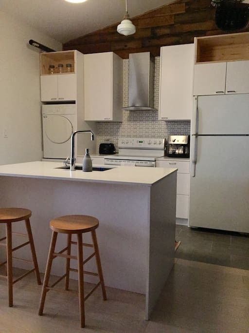 The modern kitchen supports your stay with style and function, complete with all you need to dine in, enjoy a few drinks before you hit the town or to help you take care of your chores - complete with a range of great features from the large island with breakfast bar style seating, to the fully functional washer and dryer