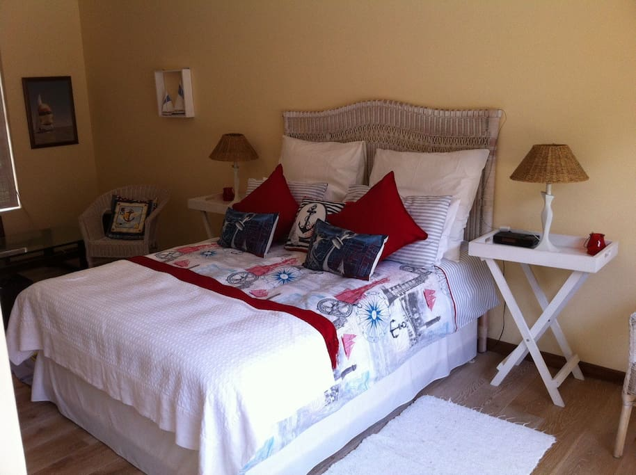 The larger bedroom, with TV and access to main Courtyard.