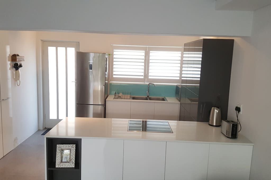 Kitchen fully equipped with appliances, bright and modern.