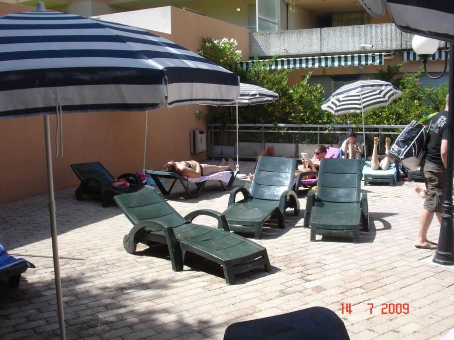 Transats et parasols aux abords de la piscine