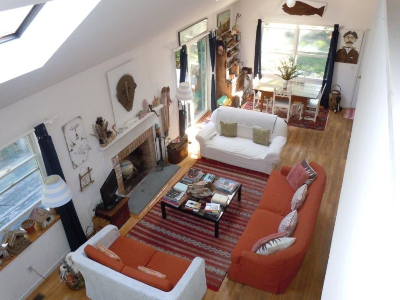 Living room and dining room, open plan, airy with skylights and sliding doors to deck