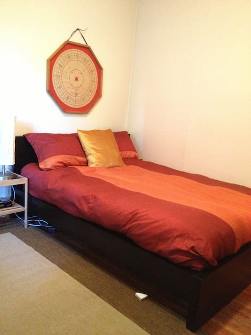 Full size bed with firm mattress and duvet, bedside lamp and iphone clock