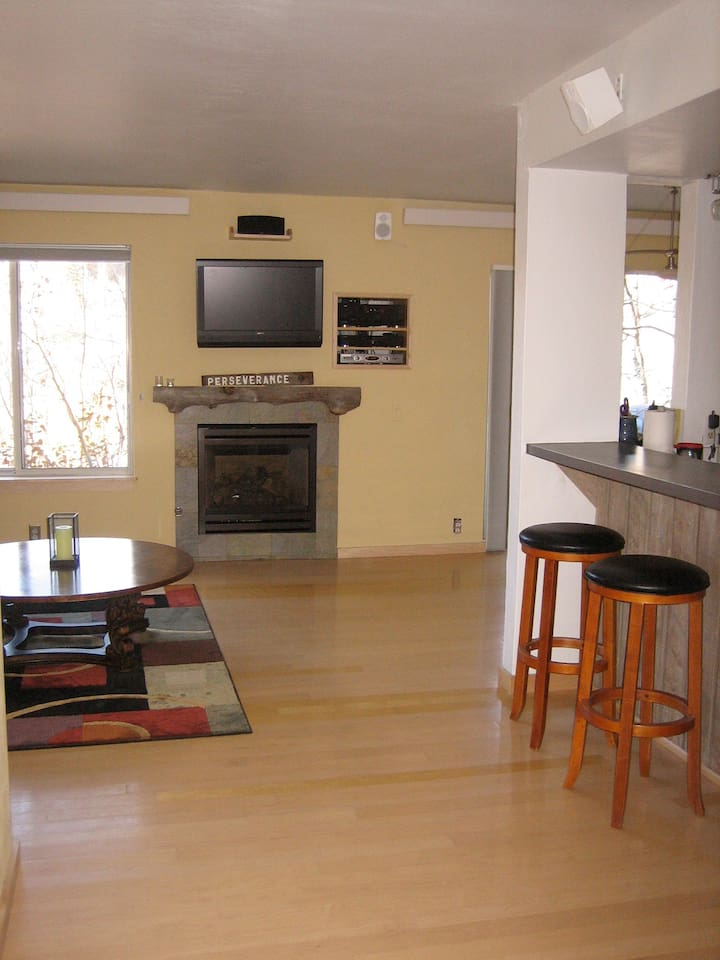 View as enter main living spaces showing gas fireplace and bar seating in front of kitchen.