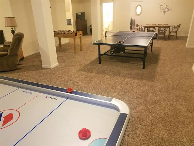 All the game tables, plus a table with six chairs (more available), cabinet with board games in it, mini-frig.  Door to bathroom and door to bedroom are both visible between the cabinet and the dining table.