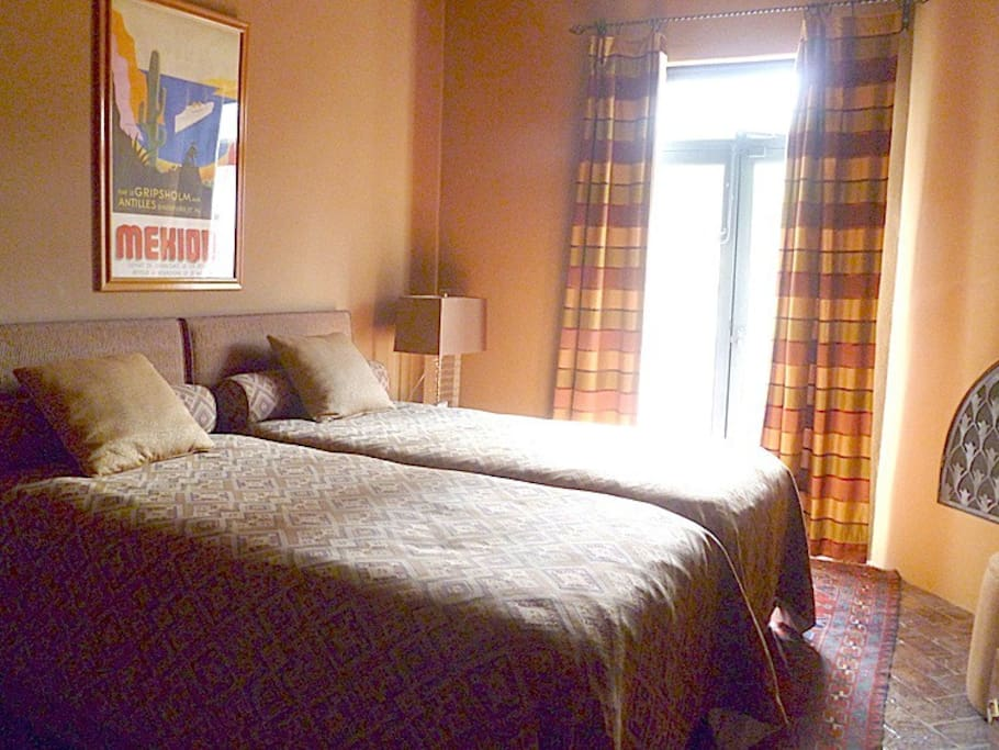 Bedroom has two single beds, narrow terrace, ceiling fan and fireplace.