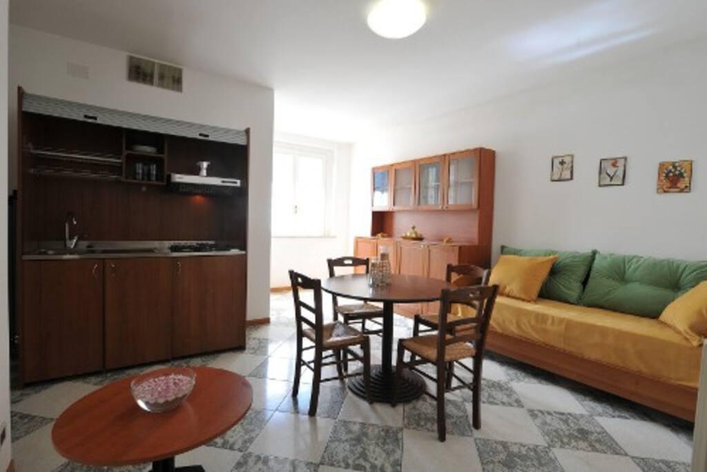 Soggiorno con doppio divano letto, angolo cottura e TV, con accesso balcone