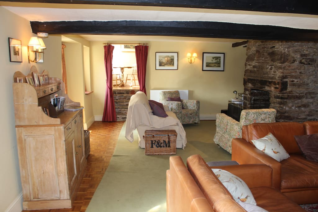 View of the double-length living room with log burner and open fire. French windows onto the sunroom.
