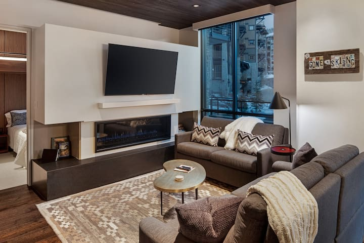 Living room with a comfortable sleeper sofa, large Sony 4k TV, and gas fireplace.