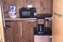 The cabinets have two types of iron ,microwave small refrigerator, disposable tableware ,Electric stove on which to cook food, coffee machine , 2 bottles of water .