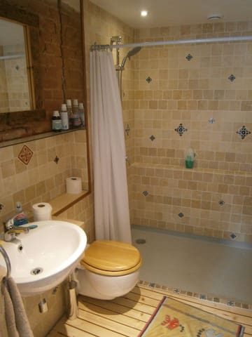 Natural limestone tiled bathroom complete with fossils - look for them while showering :-)