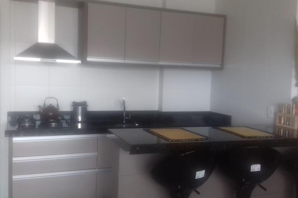 Cozinha com bancada; à esquerda a lavanderia