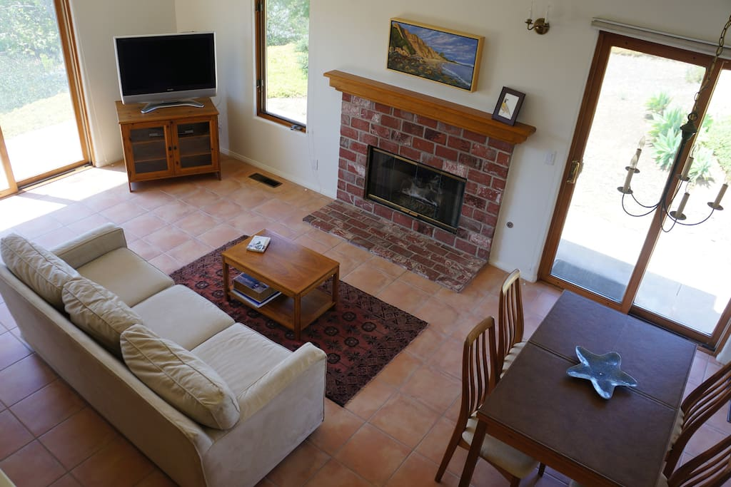 Spacious living room with flat screen TV and sliding doors out to the orchard and patio