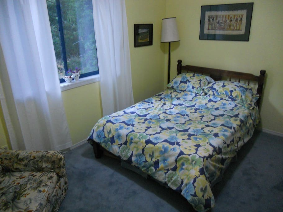 Second bedroom has double bed, comfy lounge chair, forest views