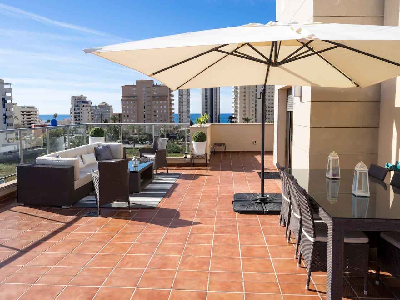 Terraza principal de  90 metros cuadrados con zona de comedor con sombrilla, sofá y hamaca doble.