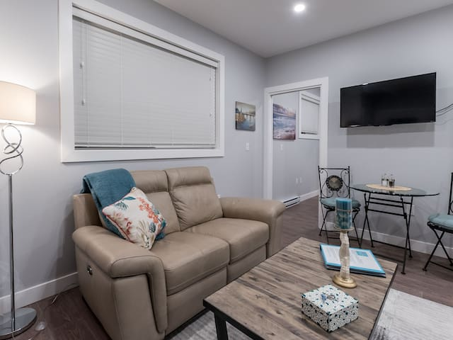 A leather reclining sofa, TV and kitchen nook table, small but cozy