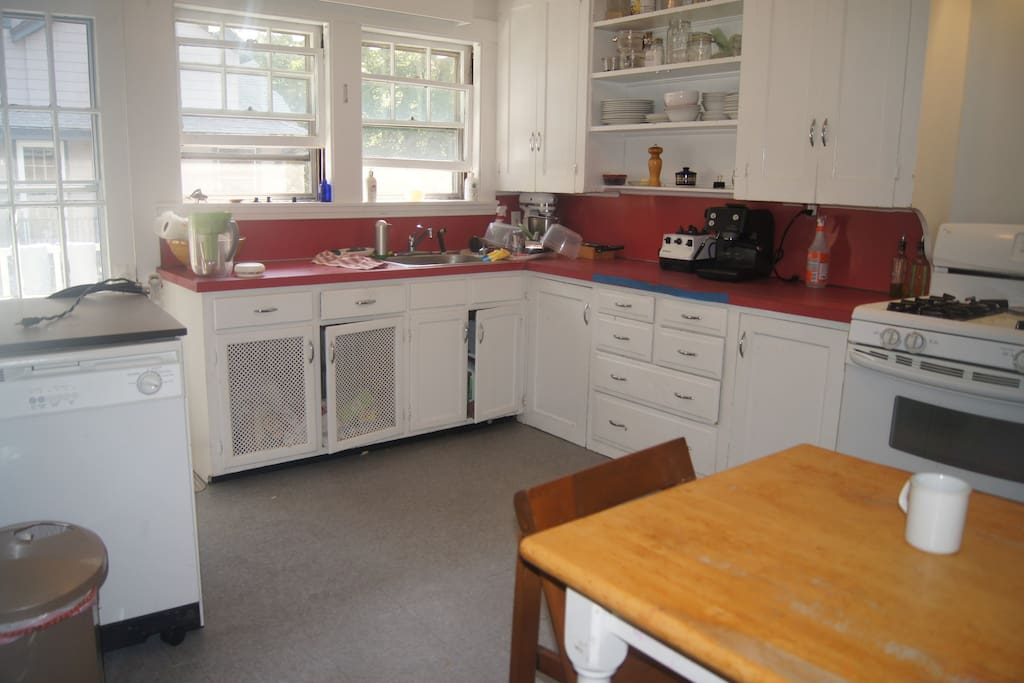 Kitchen with gas range, dishwasher and small table.