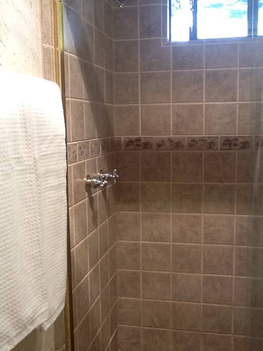 Remodeled bath with ceramic tile shower and thick spa towels