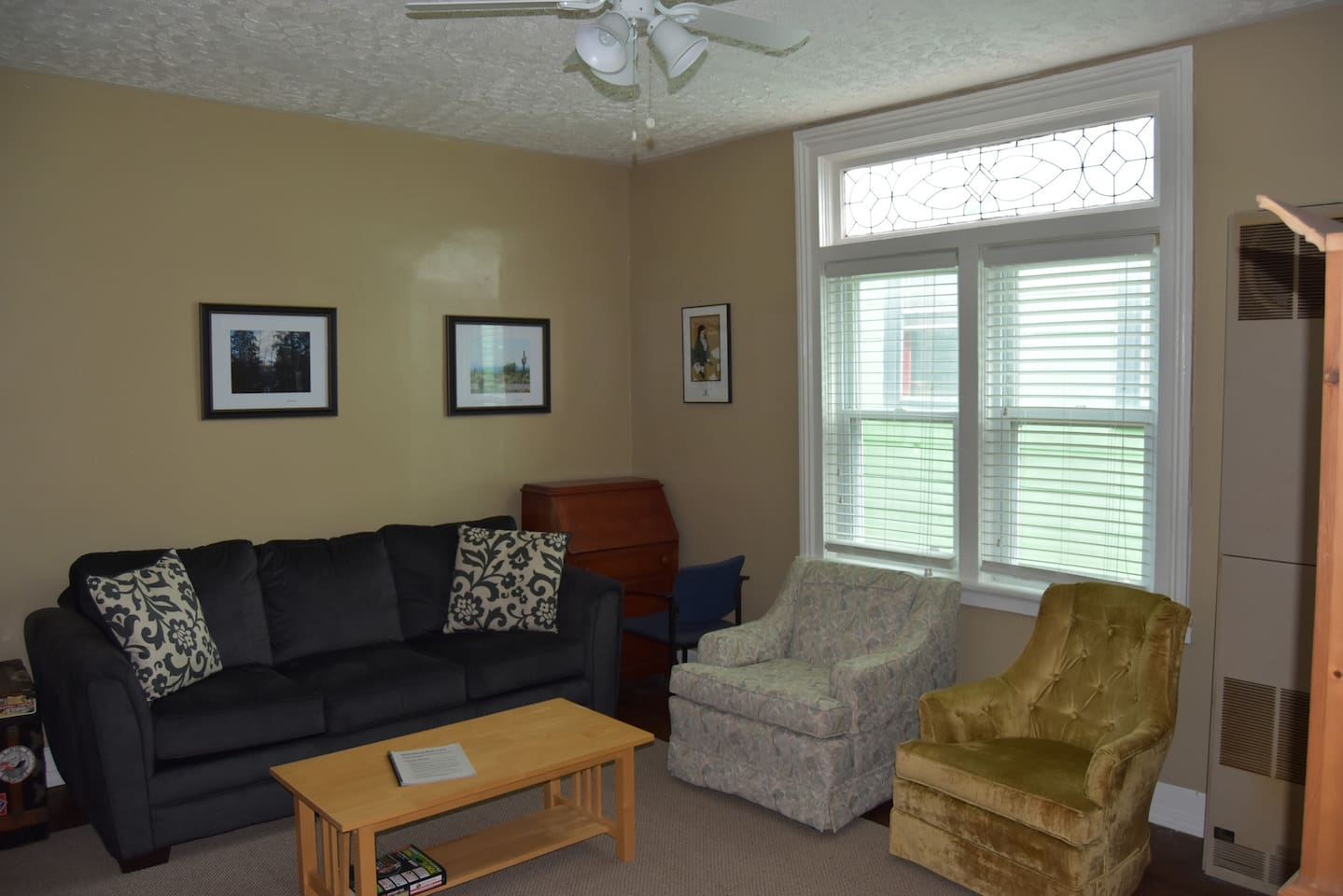 Spacious sitting room with comfortable sofa and chairs along with writing desk.
