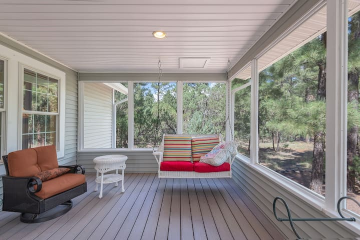 The charming screened-in back porch is the perfect spot for enjoying the greenery and fresh mountain air.