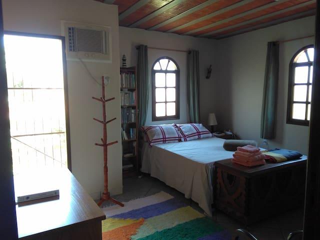 Vista do quarto pela porta de entrada. Cômoda, cabideiro, baú, cama de casal, tapete, estante de livros, luminária para leitura, mesa de cabeceira com abajur, cadeira, prateleira e móvel para malas.
