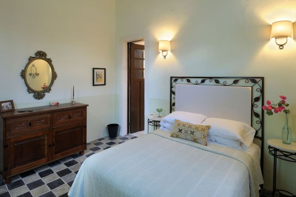 Another view of guest room showing doorway to bath. There is also a window that opens to the garden across from the bed.