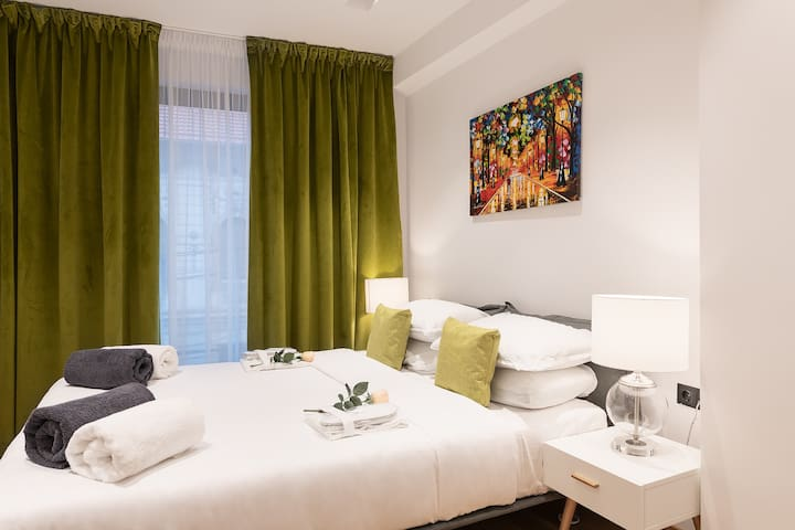 Green master bedroom-window view -the second bedroom of the apartment has 20 sqm. A comfortable king size bed and bedside tables similar to that found in the 5* hotels are the central part of the room. Green blackout curtain are made of finest velvet