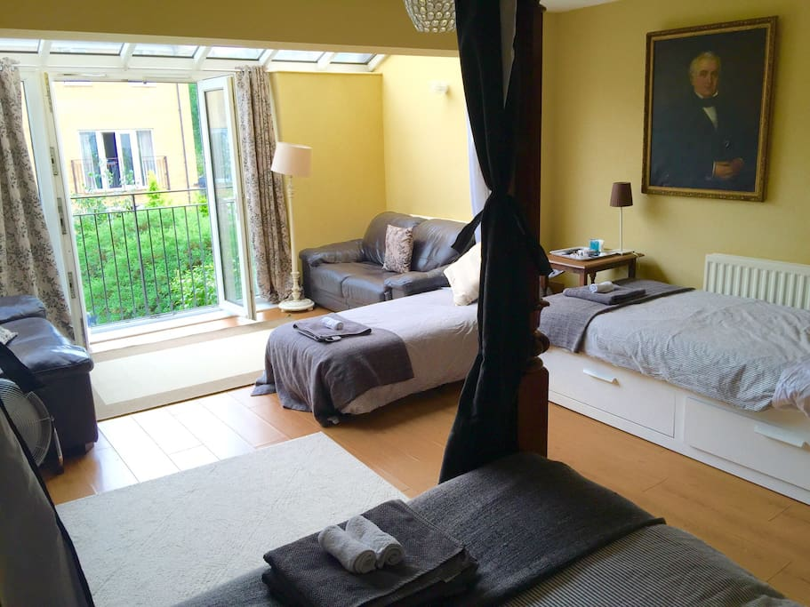 You can see from our four poster bed we have additional beds  and seating looking over the garden though a French balcony . This room is spacious unlike many hotel rooms very suitable for families.