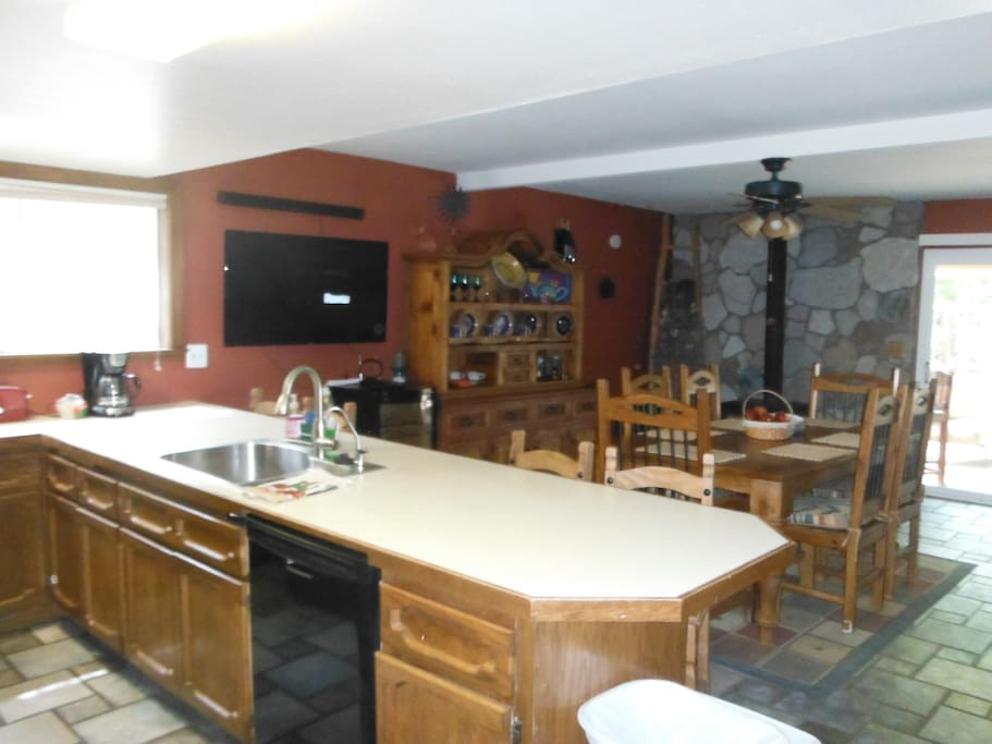 Kitchen, with gas stove, large refrigerator, bar and table.