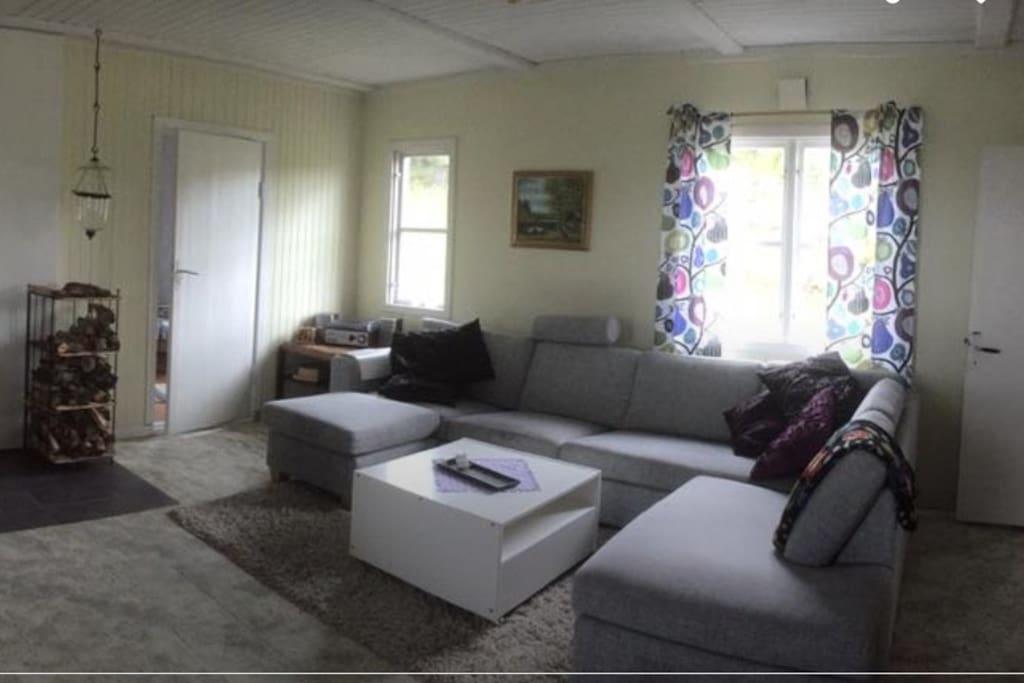 Stort sällskapsrum med kamin och matbord.
