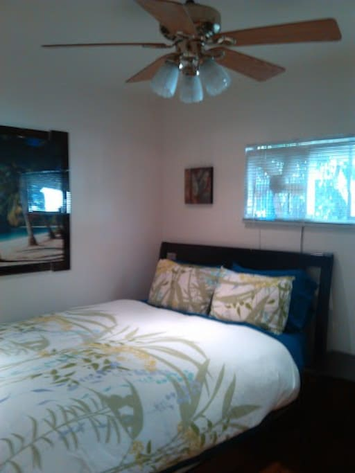 Lovely queen bedroom with tropical wall art and decor and ceiling fan