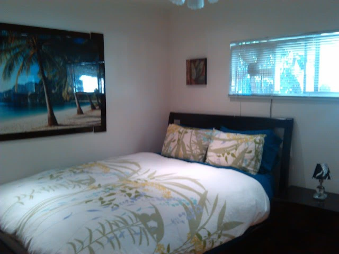 Lovely queen bedroom with tropical wall art and decor