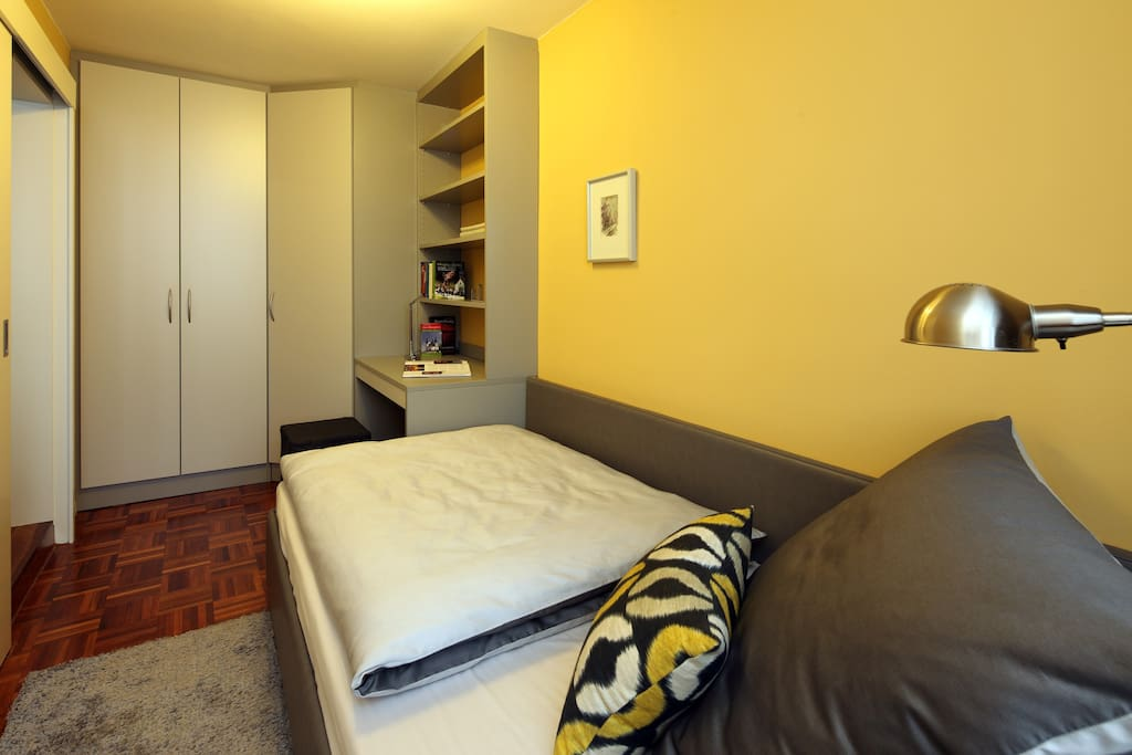 Im Schlafzimmer steht ein Einzelbett. Daneben befindet sich ein kleiner Schreibtisch mit guter Beleuchtung.