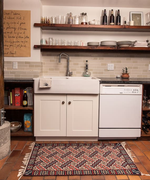 Fully remodeled kitchen includes a farmhouse sink, dishwasher, gas range.