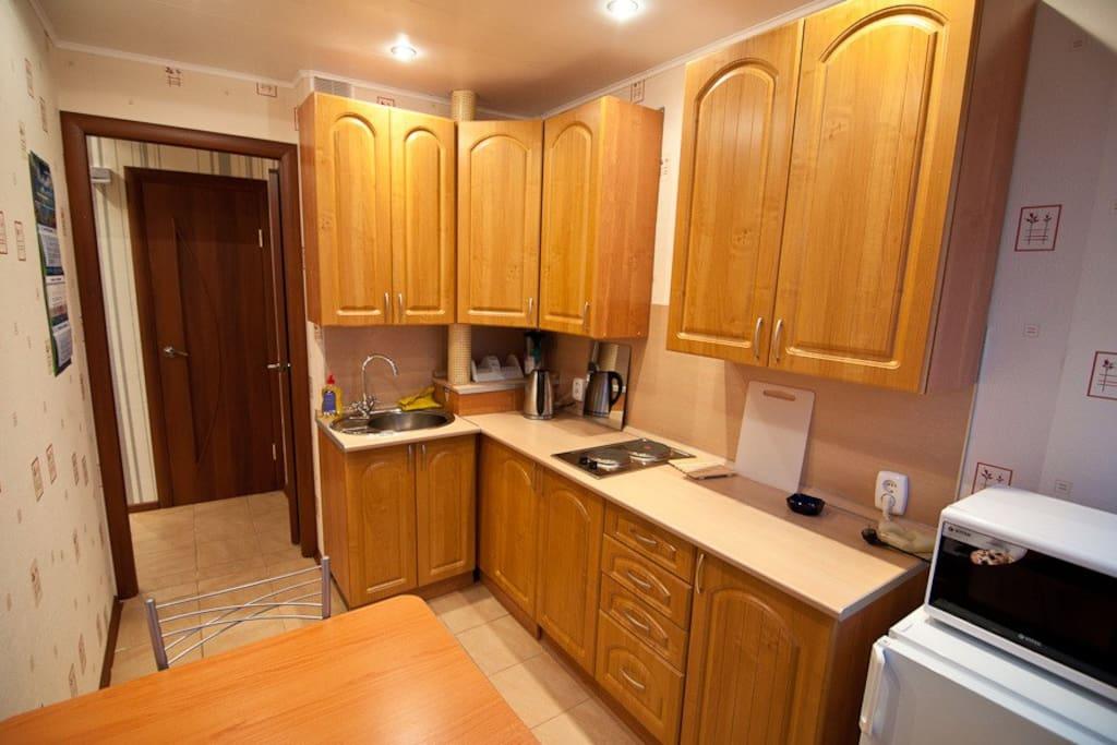 Полноценная кухня с электрической плиткой, чайником, микроволной печью и холодильником.