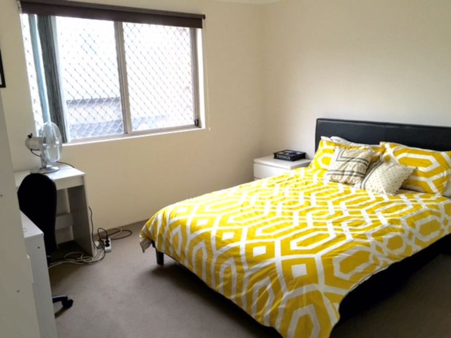 Queen sized bed, wardrobe with hangers and drawers, desk area