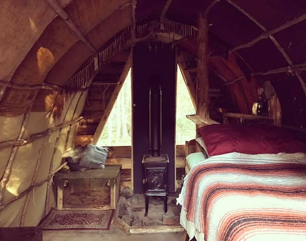 The cozy inside of our rustic hut. The first tiny home we ever built. Made with bent maple saplings.