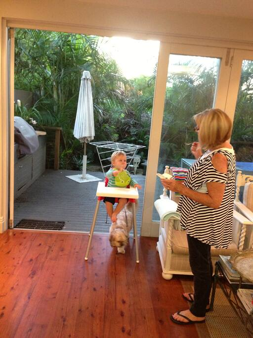 Downstairs with doors leading out to deck ,garden , Helen Webb and visitor grandson Jack plus dog eating spilt food