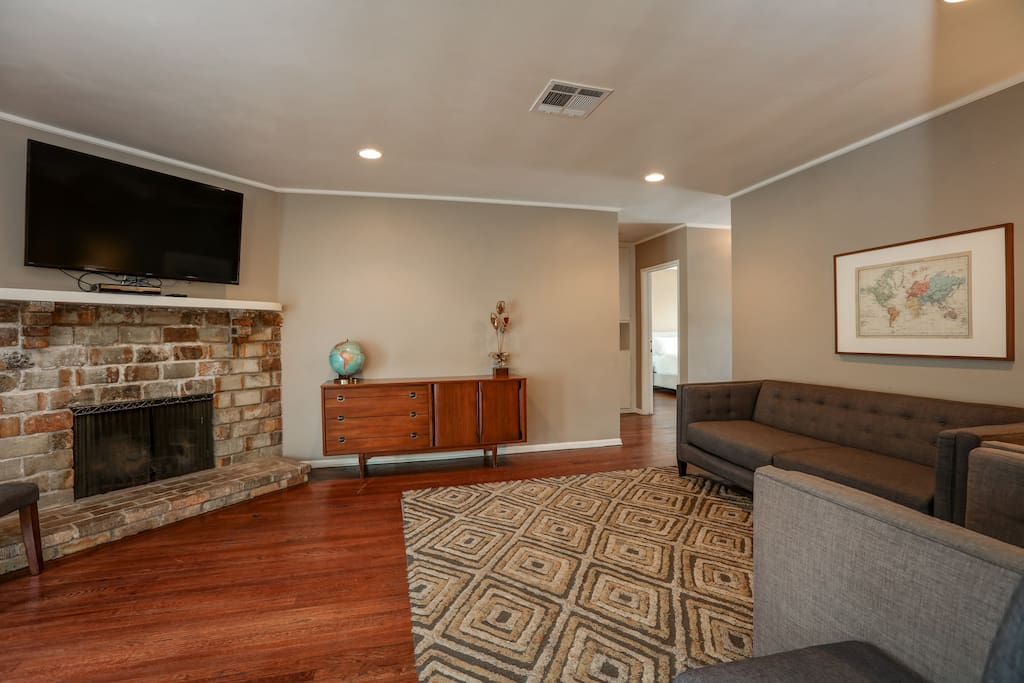 """A 52"""" wall-mounted TV hangs above a large stone fireplace."""