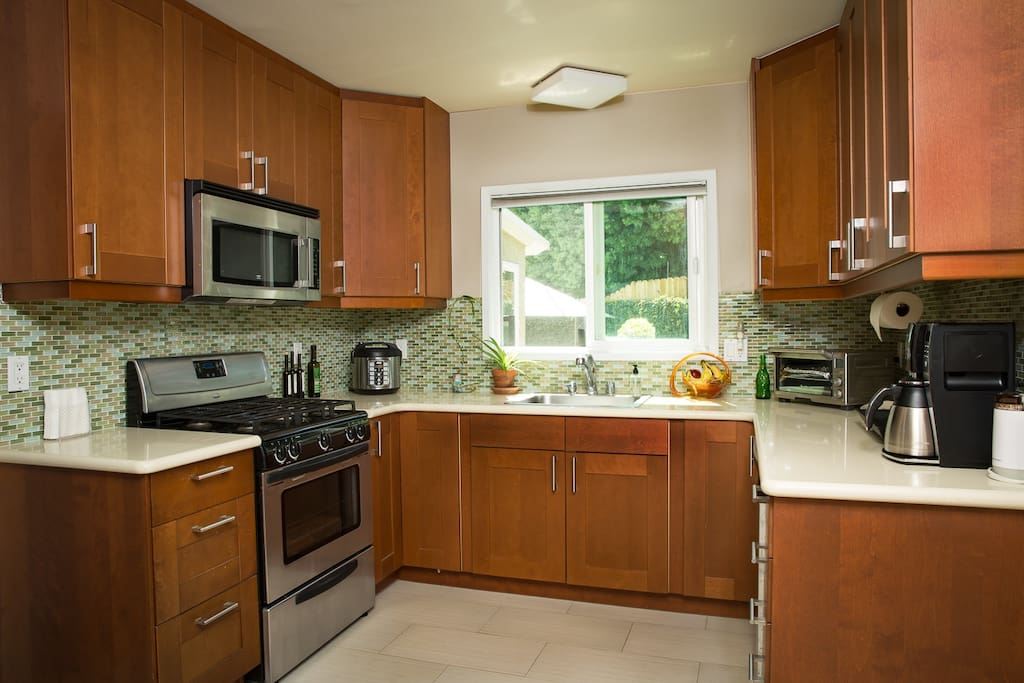 Modern kitchen with stove/oven, microwave, rice/slow cooker, toaster oven, coffee maker w/timer and dish washer.