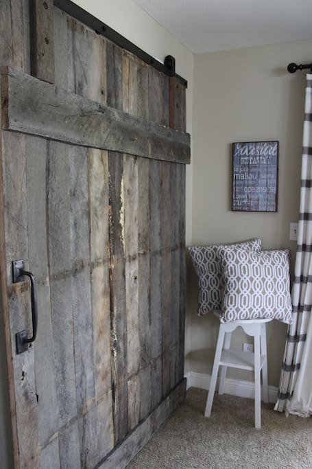 Rustic barn doors close off back living room for privacy.