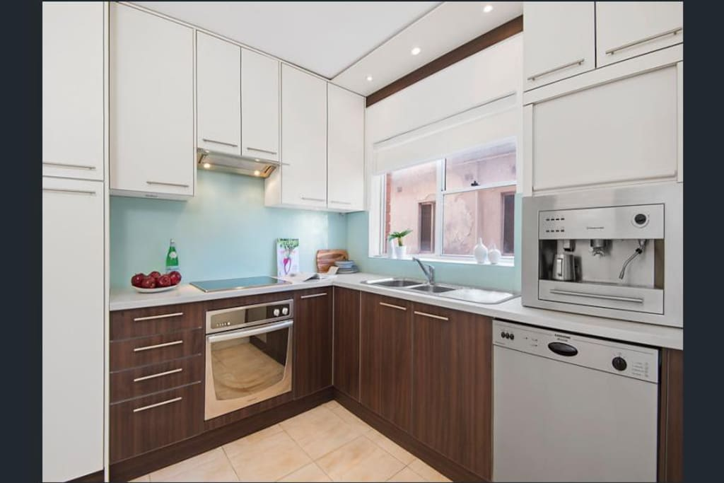 A fully equipped, sleek stone-topped kitchen, stainless steel appliance