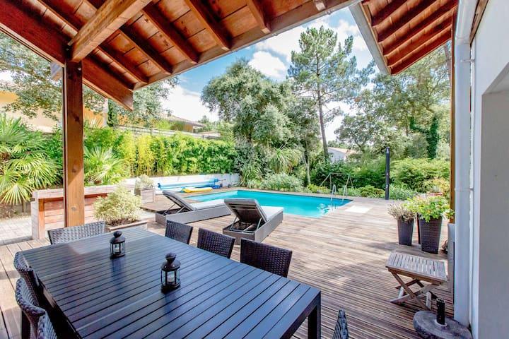 Grand deck autour de la piscine avec transats, espace repas ombragé pour 8 personnes, barbecue et plancha.