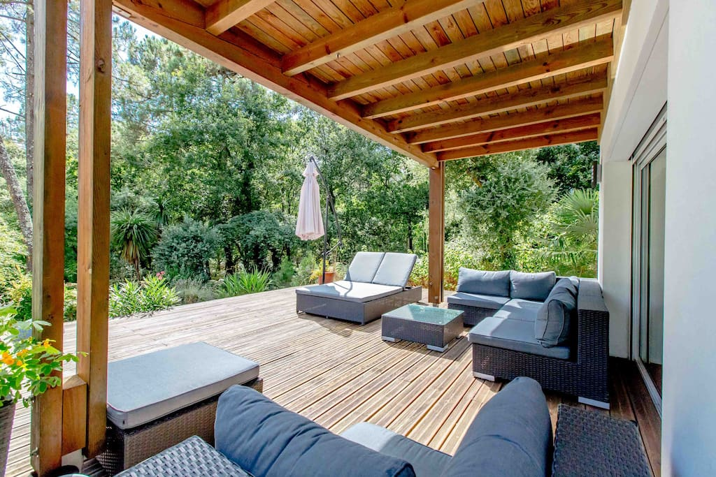 Espace salon extérieur avec vue plongeante sur la forêt..