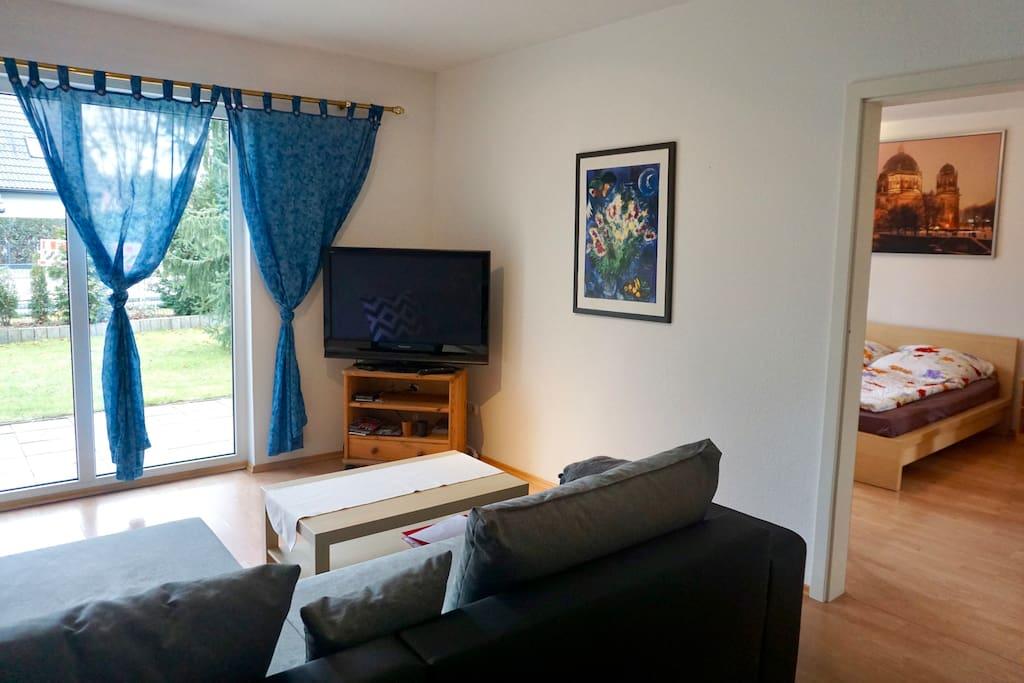 Wohnzimmer mit einer großen Fensterfront und einem Flachbildfernsehr