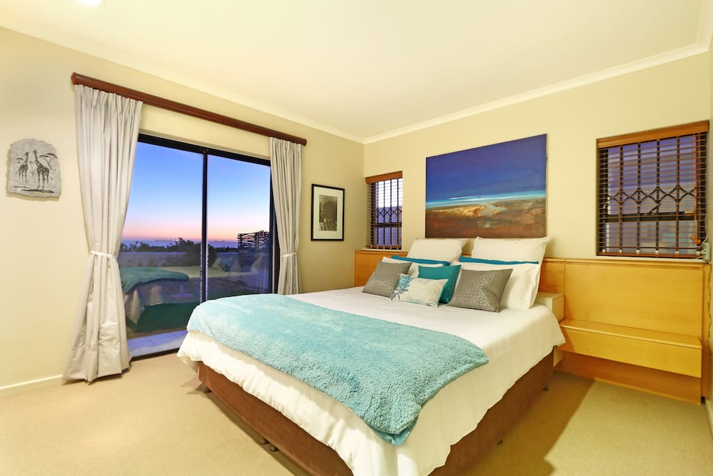 King size bed with ample cupboard space.  Sliding doors opening onto a lush green garden with direct access to the beach.